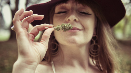 Close up of young woman smelling cannabis bud