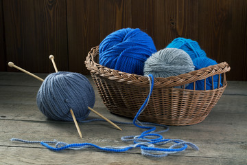 Balls of colored yarn in a basket on a wooden table