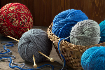 Multi-colored yarn in a wicker basket and knitting needles