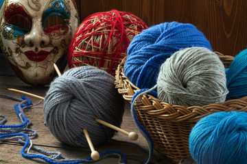 Knitting needles, wool balls and carnival mask on a wooden table