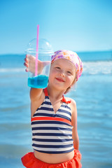 Happy little girl in  swimsuit with blue cocktail on the beach. Summer. Vacation. Sea. Ocean
