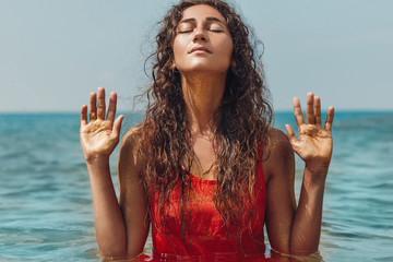 beautiful young woman in red dress in water showing her hands with golden pollen