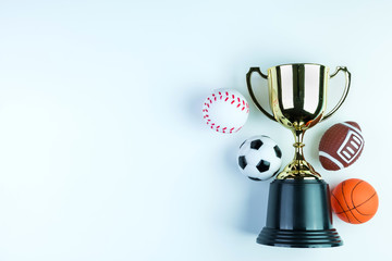 Golden trophy, Football toy, Baseball toy, Basketball toy and Rugby toy isolated on white background with copy space.Concept winner of the sport.