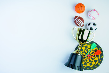Golden trophy, Football toy, Darts with crotch, Baseball toy, Basketball toy and Rugby toy isolated on white background with copy space.Concept winner of the sport.