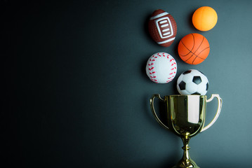 Golden trophy, Football toy, Baseball toy, Ping pong ball, Basketball toy and Rugby toy isolated on black background with copy space.Concept winner of the sport.