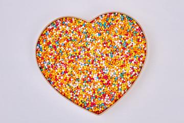 Sprinkle dots, heart shaped box. Sugar sprinkles on white background. Saint valentine present.