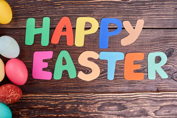 Happy Easter lettering on wood. Colored eggs and paper letters. Made with kindness.