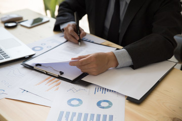 Businessman analyzing charts and graphs and signing document