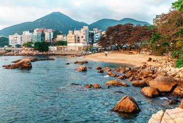 Rocky sea shore and small sandy beach of Stanley Bay in Hong Kong. Beautiful scenic landscape with water, mountains, rocks and buildings
