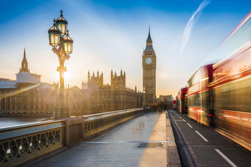 Photo sur Plexiglas Londres London, England - The iconic Big Ben and the Houses of Parliament with lamp post and moving famous red double-decker buses on Westminster bridge at sunset with blue sky