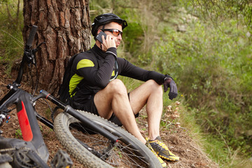 Young European cyclist in sportswear resting in woods talking on mobile phone with friend looking serious while sitting under tree by his electric bike, having small break while exercising outdoors