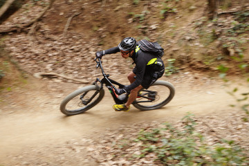 Motion picture of young Caucasian professional rider in helmet, glasses and sportswear speeding down forest trail on booster bike duing intensive workout while preparing for cycling competition