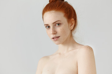 People, youth, beauty and skin care concept. Portrait of beautiful young redhead woman posing topless looking at camera with subtle mysterious smile, having freckles all over her face and shoulders