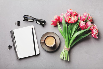 Coffee, clean notebook, eyeglasses and beautiful tulip flower on stone table top view in flat lay style. Woman working desk with cozy breakfast.