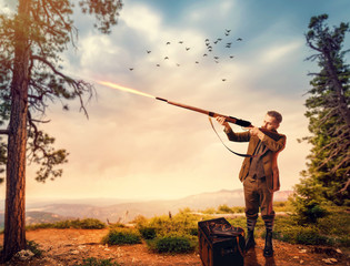 Duck hunter in hunting clothing aims an old rifle