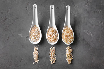 Three ceramic spoons with organic white quinoa grains on dark background