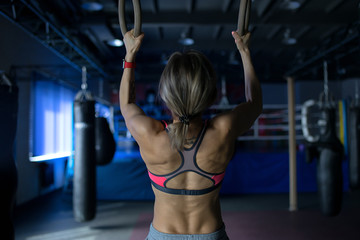 Young woman doing a pullup ongymnastic rings, in the gym
