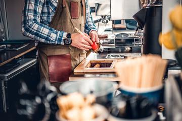 A man cleans coffee machine with a tassel.