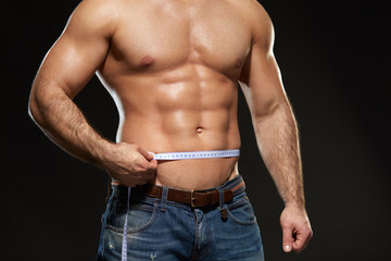 Closeup Of Sexy Muscular Man Body With Measurement Tape