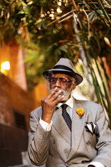 Senior man smoking a cannabis joint while sitting outdoors
