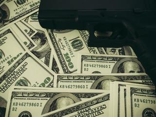 Moneys and gun concept.