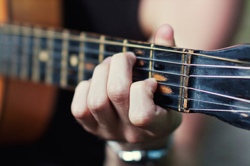 Practicing in playing guitar. Handsome young men playing guitar,Closeup of blurry male hands playing the guitar,music concept