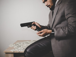 Money and power, Senior gangster with gun, in suit at the table.