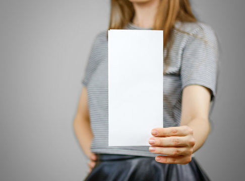 Woman showing blank white flyer paper. Leaflet presentation. Pamphlet hold hands. Girl show clear offset paper. Sheet template. Booklet design sheet display read first person