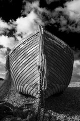 Black and white close-up image of the bow of an abandoned wooden fishing boat