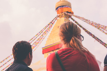 European traveler with her guide at boudhanath stupa on faded vintage tone