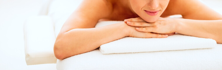 Closeup on happy young woman laying on massage table