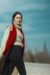 Young beautiful girl model in vest coat of red and beige color and in turtleneck