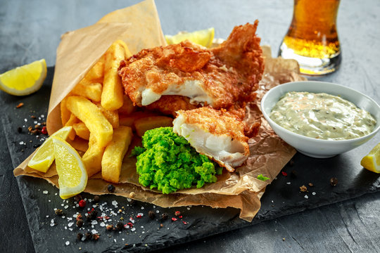 British Traditional Fish and chips with mashed peas, tartar sauce on crumpled paper with cold beer.