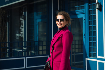 stylish young woman in a pink coat and sunglasses on the street