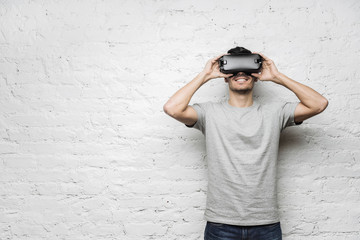 Close up of caucasian male wearing grey t-shirt and goggles, experiencing virtual reality. European man playing video games using oculus, standing against white brick wall. Technology, gaming concept