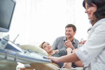 Loving couple attending doctor for pregnancy ultra sound procedu