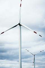 Two wind turbines standing still in front of a cloudy sky