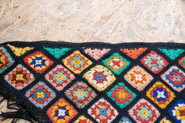 Diagonal layout of handmade blanket made from granny squares - copyspace