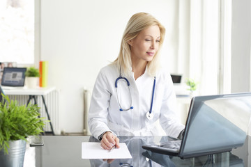 Shot of a female doctor working on medical expertise while sitting at desk in front of laptop.