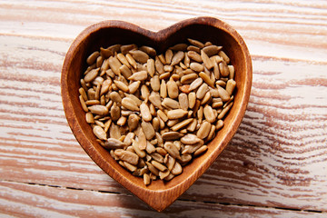 Sunflower seeds in wooden heart shape bowl