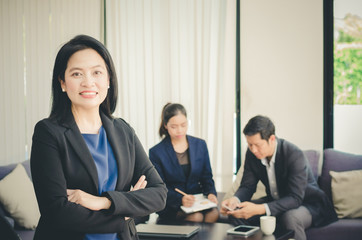 Asian business woman standing front of her teams in office.
