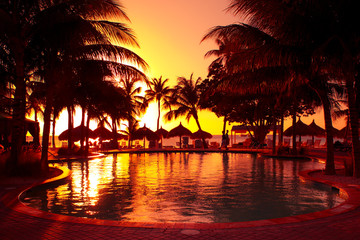 Tropical resort at sunset with pool, palm trees and huts
