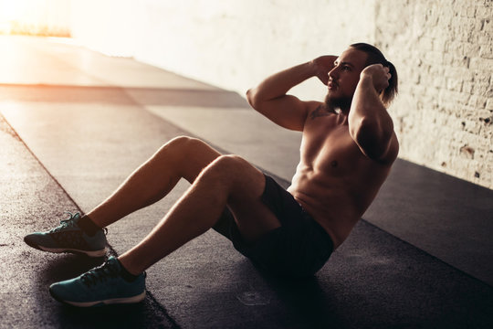 Male fitness model doing sit ups and crunches exercising abdominal muscles, six pack visible wearing no shirt