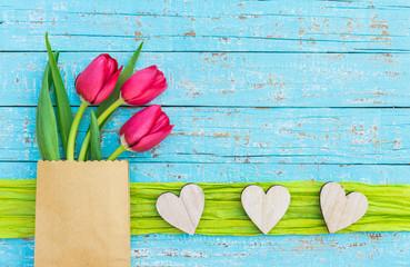 Rote Tulpen mit Herzen auf Holz Hintergrund Blau und Textfreiraum
