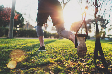 Healthy lifestyle concept.Muscular athlete exercising trx outside in sunny park.Great TRX workout.Young handsome man in sportswear doing exercising outdoors.Blurred background,flare.