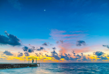 Beautiful sunset with sky over calm sea  in tropical Maldives island .