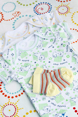 newborn baby clothes set: two t-shirts and knitwear toddler socks on colorful blanket background with copy space