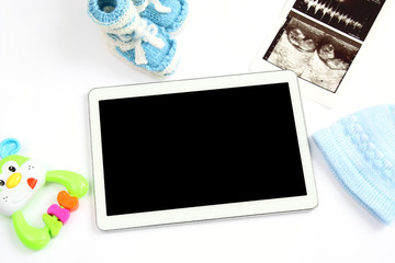 concept of extending family and expecting for baby: blank screen tablet pc, first picture ultrasound scan of baby, clothing for newborn - hat and booties, colorful rattle on white background