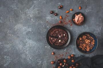 Chocolate cake, chocolate muesli and chocolate ice cream on dark background. Flat lay, top view, copy space