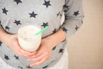 Young woman with a big glass of healthy smoothie served with a straw and oats. Hands holding milkshake. Stars background. Dairy snack or breakfast.